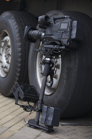 leaning on the truck: professional video camera with stabilization system Steadicam stands at a trucks big wheels
