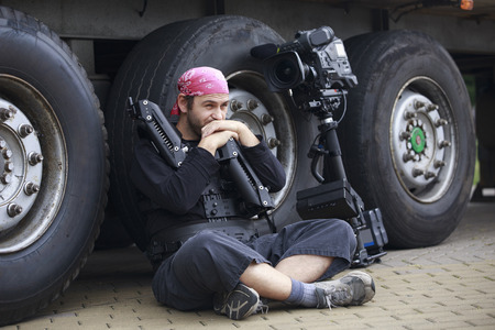leaning on the truck: thoughtful cameraman sits on the ground leaning on the wheel of a truck. He weared in steadicam harness with arm and the camera stands beside. Stock Photo