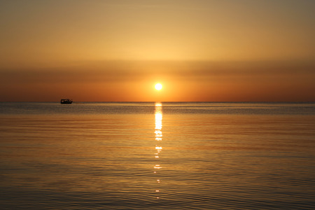 Rising Sun over the sea with a light path and a boat sails