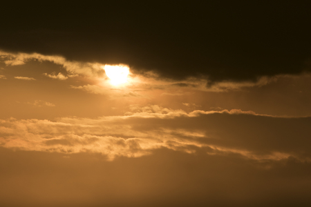 Orange sunset sky with a Sun behind the stormy cloud