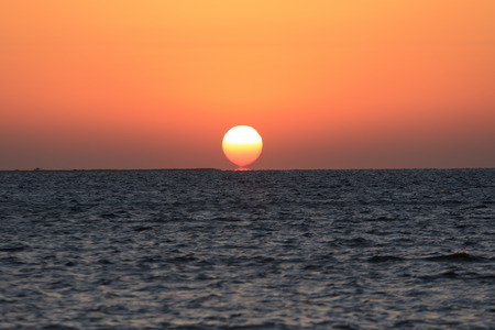 rises: Sun rises up above the sea with calm water and orange sky Stock Photo