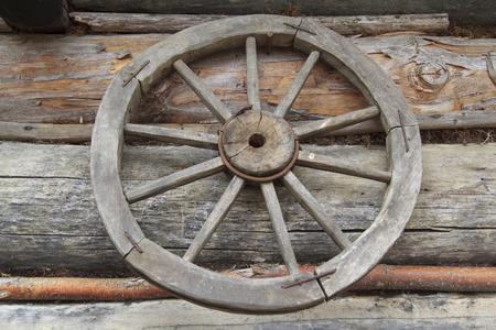 old vintage rural self-made wooden wheel at wall in ukrainian authentic village Kolochava
