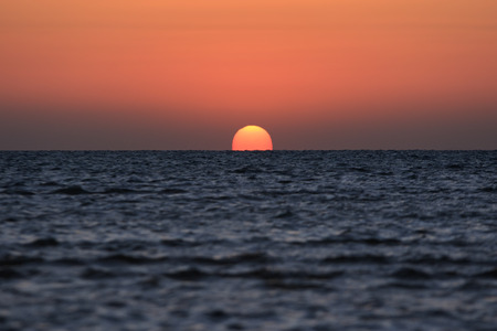 rises: Solar disk rises up above the Red Sea with sky painted in red