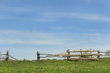hunker: Old rickety wooden fence in ukrainian village with blue sky and green blooming field background Stock Photo