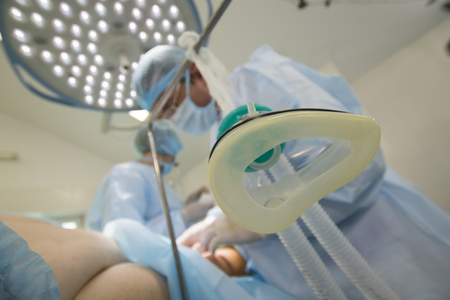 Mask for an narcosis close-up in foreground of surgery