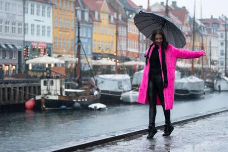 Young woman in pink coat dances with umbrella during the rain in Copenhagen, Denmark