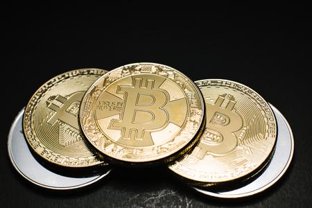 Bitcoin. Gold Bitcoins on a one hundred dollar bill close up Stock Photo