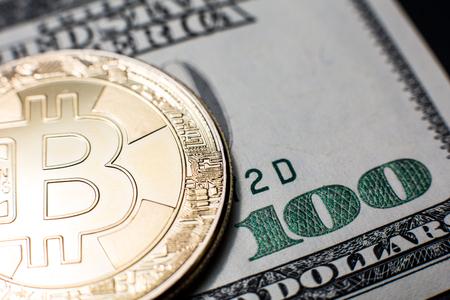 Bitcoin. Gold Bitcoins on a one hundred dollar bill close up Zdjęcie Seryjne