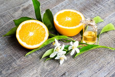 Succosa arancia tagliata in due parti e neroli, fiori di arancio, su fondo di legno rustico. Il Fiore d'Arancio è il fiore profumato degli Agrumi è utilizzato in profumeria e tè, afrodisiaco. Archivio Fotografico