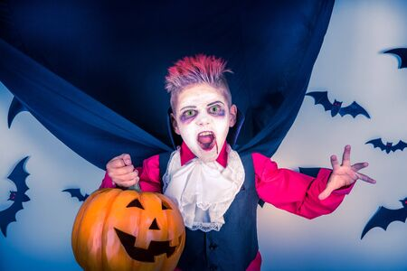 Halloween kids: little boy in a costume of vampire Dracula scares on pumpkin patch