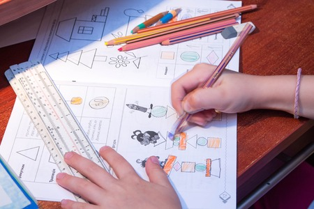assignments: The child learns. Child paint. The child is doing school homework. Stock Photo
