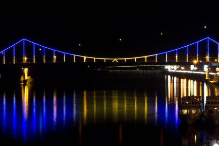 Striking a bridge across the river. The bridge in the center of Kyiv. Bright bridge across the Dnieper River.