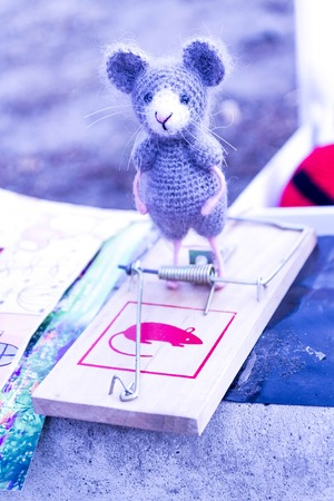 Toy mouse in a mousetrap. Knitted toy. Tied mouse. Puppet mouse.