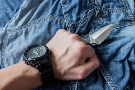 left hand: Serrated knife on jeans background in left hand.