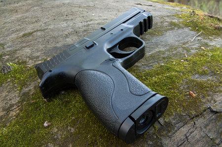 Black gun. Large stumps and moss. Tactical gun. Military gun. Sport shooting.