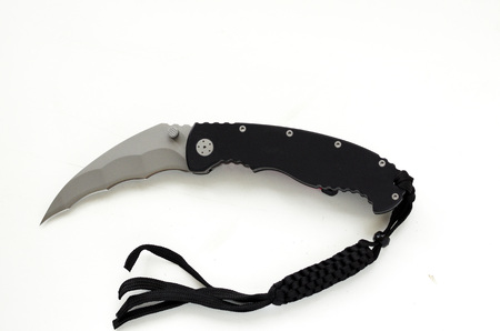 A pocket knife with a curved blade on a white background. Claw of a tiger. Claw of an eagle. Fang.