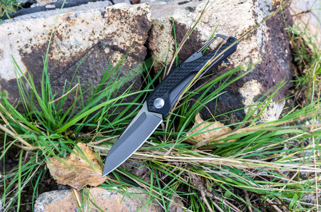 Pocket knife. Knife with a carbine. Photo knife in nature.