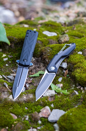 Two folding knives. Knives with different handles. Vertical frame. Photo on the background of moss.