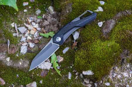 A pocket knife with a black handle and a black blade. Photo on the nature. Stock Photo