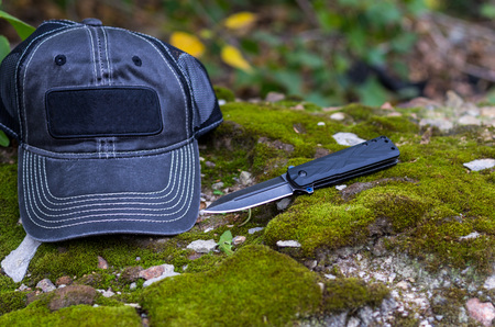 Black knife and black cap. Folding knife and baseball cap. Photo on the background of moss. Stock Photo