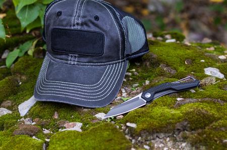 Black folding knife and black baseball cap. Photo on the background of moss. Stock Photo