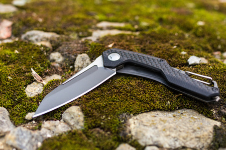 Pocket knife in a curved state. A knife on a stone and a moss.