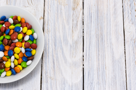 The plate is filled with sweets. Multicolored pellet. Copy space. White wooden table.