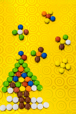 New Year's composition from multi-colored sweets. New Year tree from a child's pills. Children's composition.