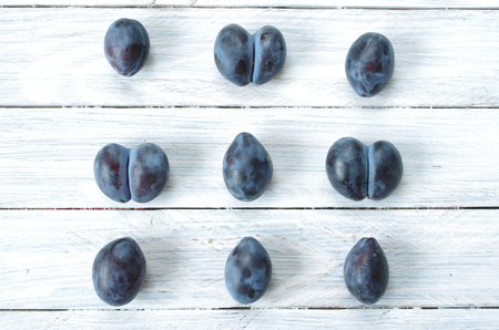 A combination of fruits. Combination of household plums. Plums on white background. Repetition of objects. One after another. Row after row.