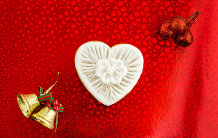 White heart and Christmas bells. Celebrating the day of lovers. Stock Photo