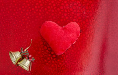 Red heart on a red background. Christmas bells.