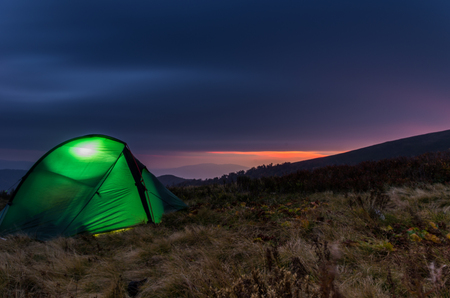 Sunset in the mountains. Tourist tent in the foreground.
