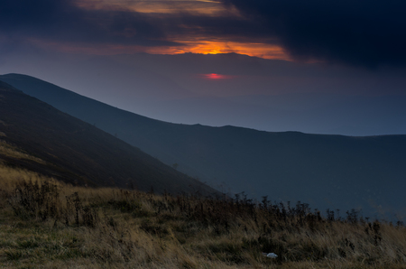 Evening landscape in the mountains. Red sun. The sun is behind the clouds. Mountain background.