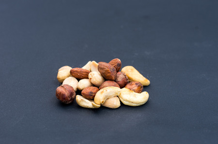 A variety of nuts on a black background. Front view.