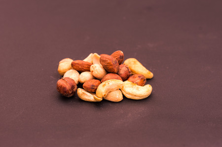 A variety of nuts on a brown background. Front view.