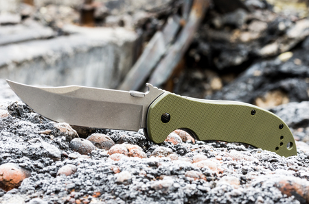 Military pocket knife close-up. Green plastic handle. Stock Photo
