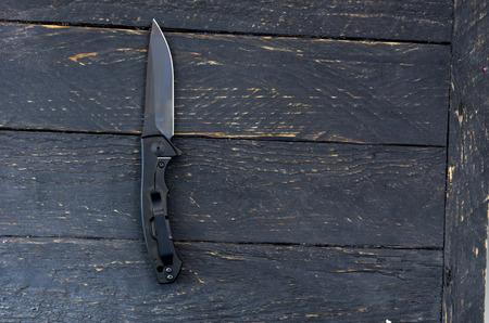 Black knife with a black blade. Dark wooden background.