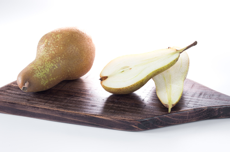 Piece of pears on a chopping board. Isolate. Front view.