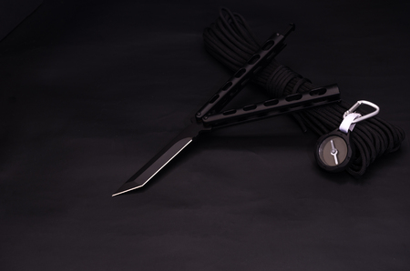 Composition of a knife and a compass. Black knife and black compass. Reklamní fotografie