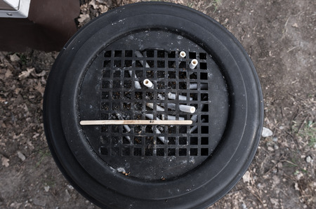 Street ashtray. Trashcan with cigarette butts. Street urn. Street garbage. Black and white.