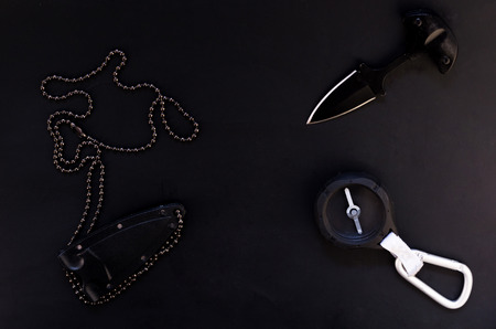 Knife and compass. Tourist accessories on a black background. Stock Photo