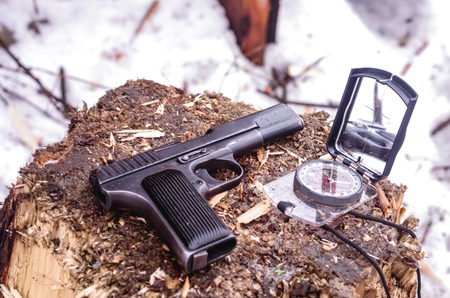 Pistol and compass on the stump. Military composition. Stock Photo