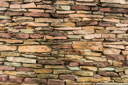 A wall of small stones. Texture of yellow stones. Stony background. Texture and patterns.