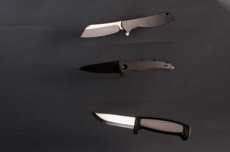 A few knife on a gray background. Three sharp knife. Knives on a gray background.