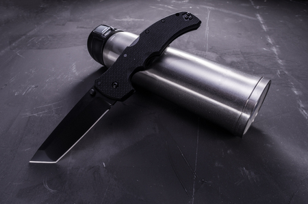 Folding knife and thermal bottle. American knife and steel bottle. Tilt view.