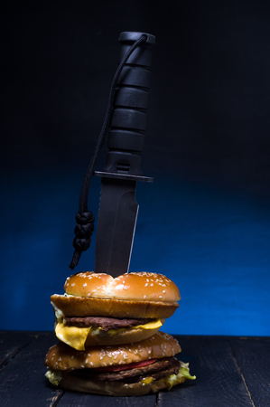 A large knife embedded in burgers. Double burger with meat. Vertical frame. Foto de archivo