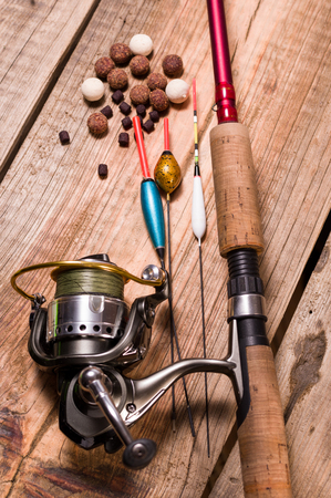 Fishing rod with a cortical handle and a fishing reel. A variety of floats. Fishing bait from boilies and pellets. Vertical frame.