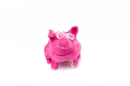 Pink pig made of clay. Sculpting pigs from ceramics. Children's handicraft. Isolate.