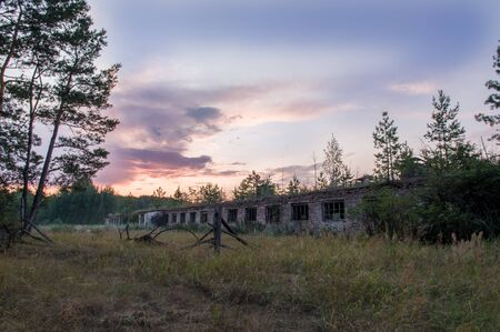 Old abandoned building. Old cowshed in the forest. Old brick building. Stock Photo
