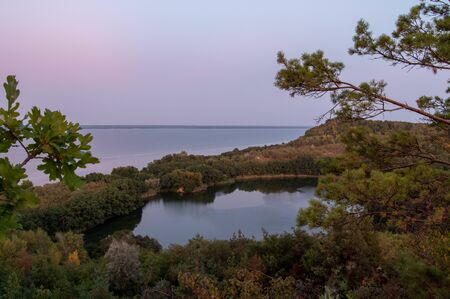 View of the lake from behind the branches. View of the lake from the forest. View of the Dnepr River.